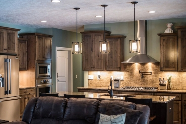 wider view of open kitchen with island and darker finish