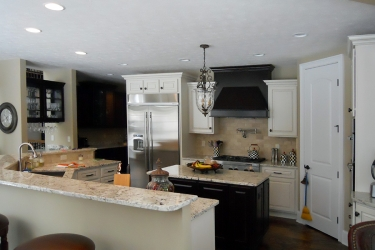 custom white kitchen with darker island and range hood